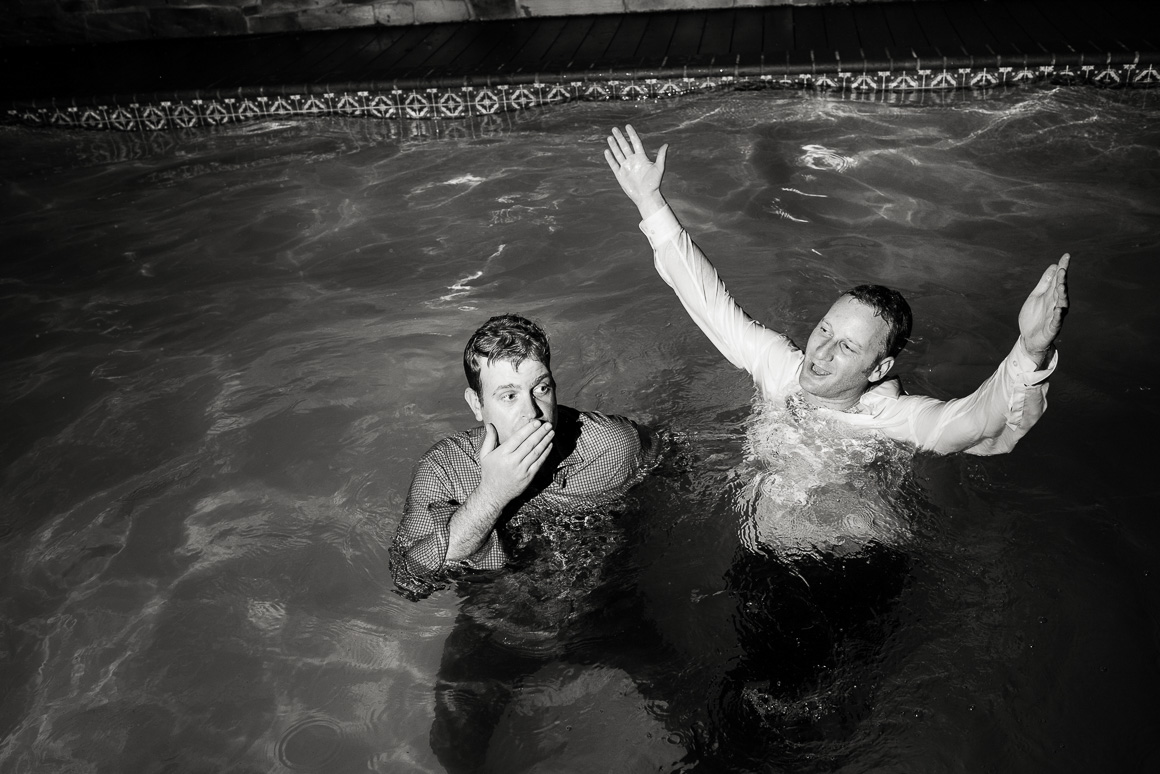 Denver LGBTQ wedding photographer captures grooms cooling off in swimming pool.