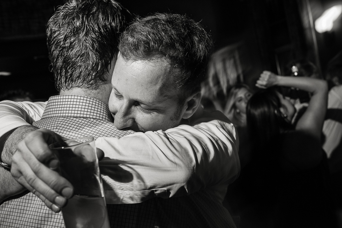 Grooms embrace by Denver LGBTQ wedding photojournalist.