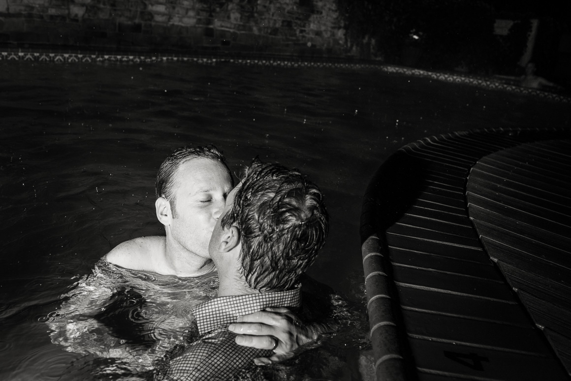 wedding reception pool newlyweds kiss water
