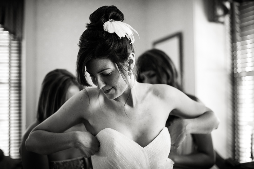 Bride putting on dress by Denver Wedding Photographer.