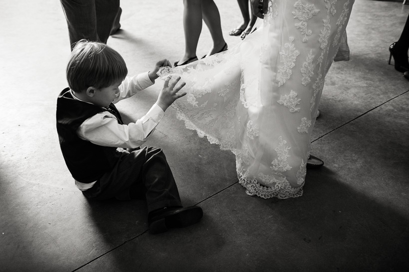 Boy at Northern Virginia wedding looks underneath bride's dress.
