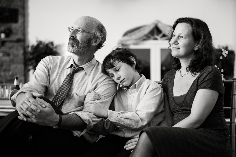 Tired boy with parents by Denver wedding photojournalist.