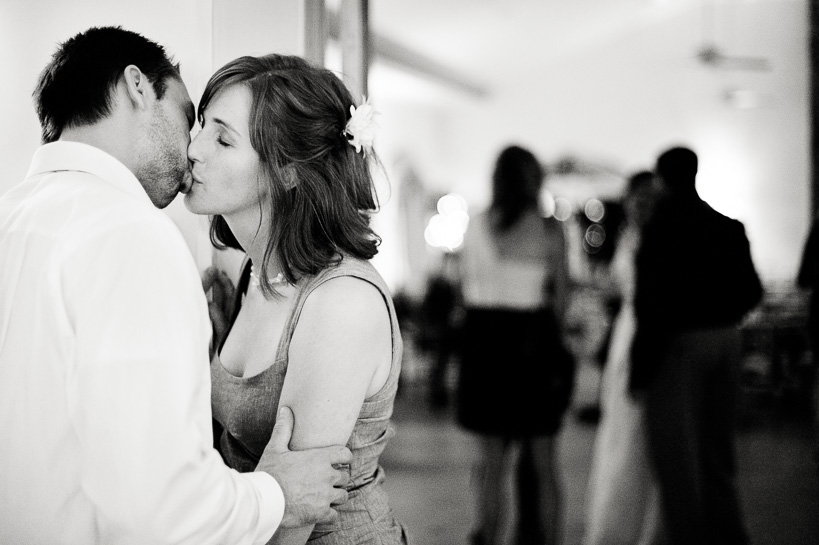 Stolen kiss away from the crowd at a wedding reception.