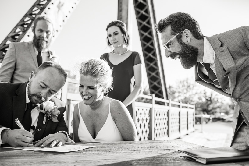 Bride and groom sign marriage license on bridge outside Coohills restaurant.