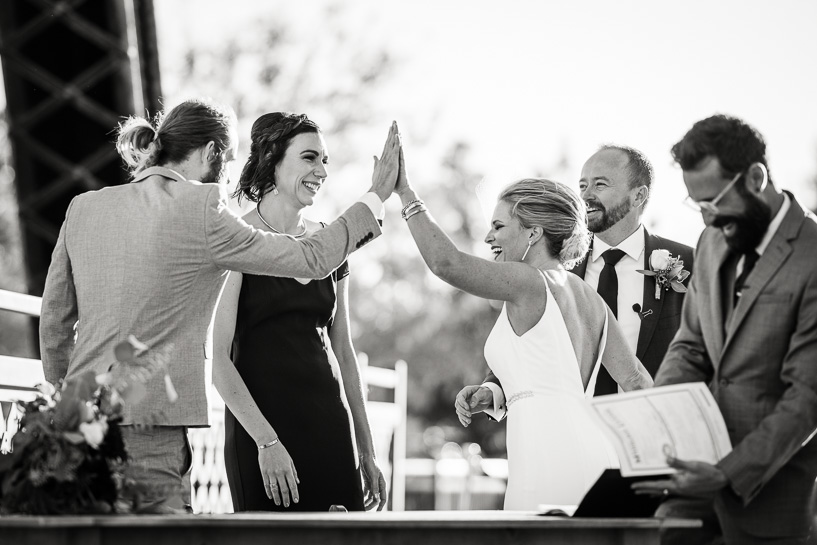 Best man gives bride high five after signing marriage license.