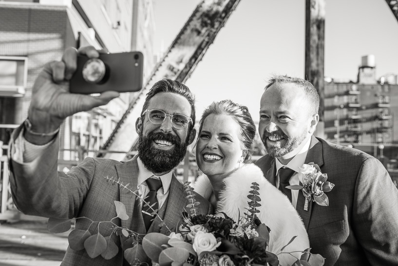 Officiant at Denver wedding takes selfie with bride and groom.