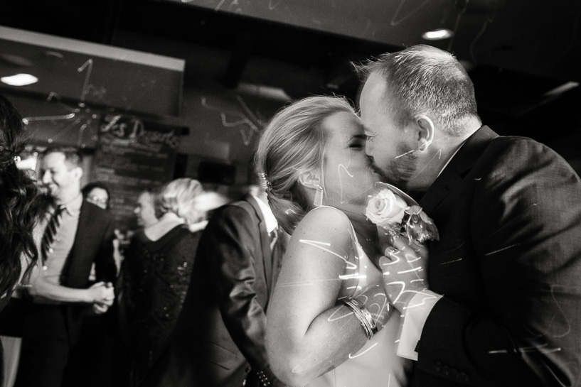Bride and groom kiss at Denver wedding reception.