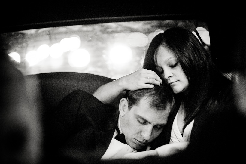 Bride and groom asleep in the back of the limo after their wedding.