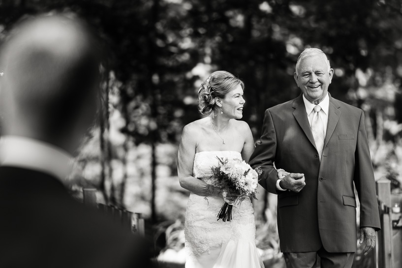 Documentary wedding photography of bride walking down aisle with father.