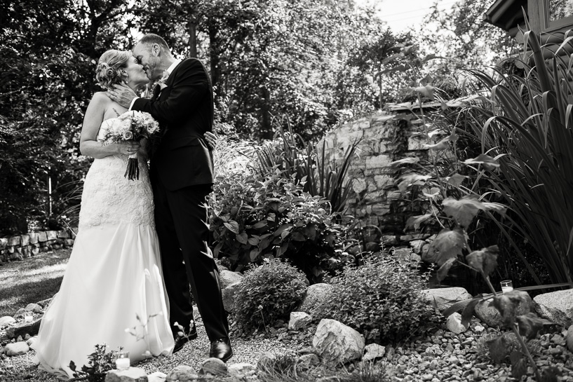 Denver wedding photojournalist captures ceremony kiss in backyard wedding.