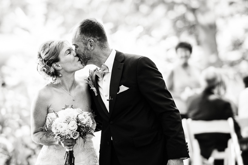Denver wedding photographer captures bride and groom kissing after ceremony.
