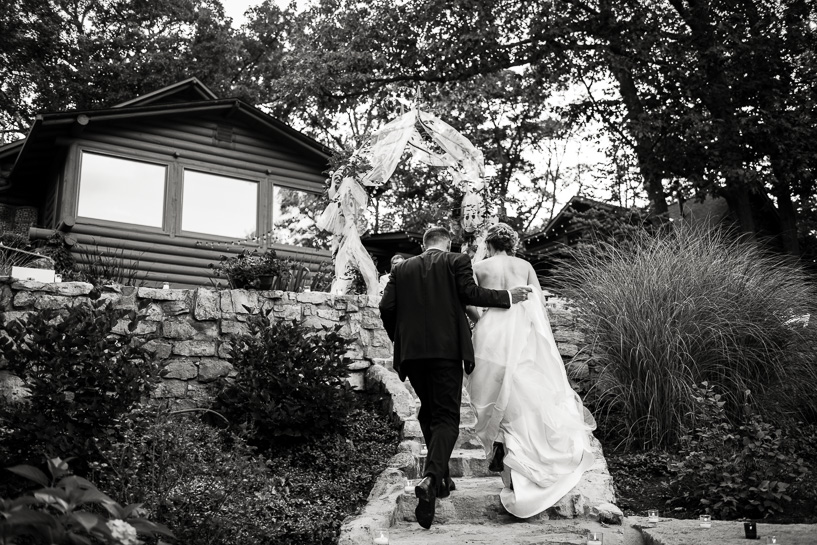 Black and white wedding photography of couple returning to their house.
