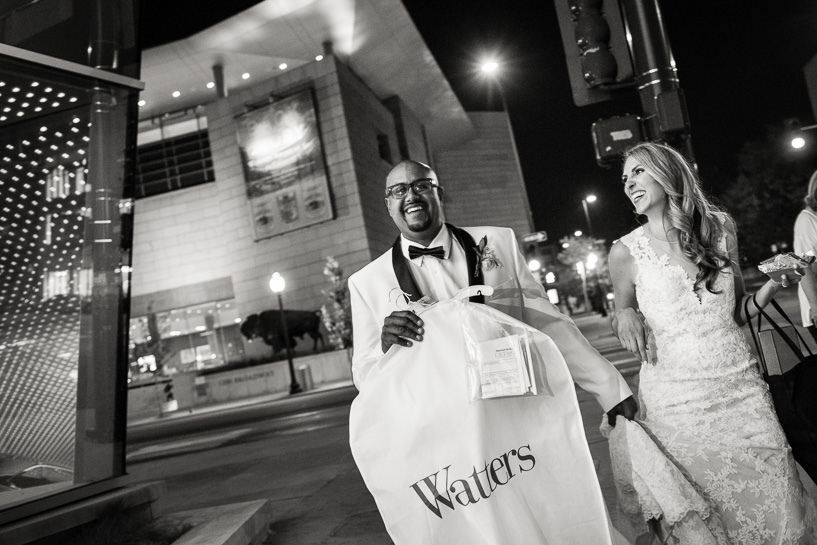 Bride and groom walk down street with clothing bags.