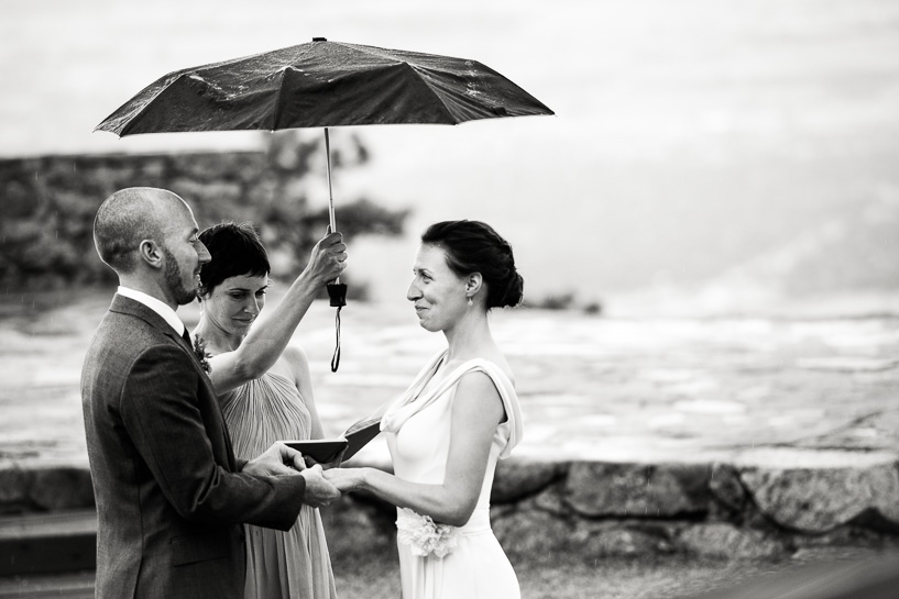 Denver wedding photojournalist captures groom slipping ring onto bride's hand while officiant holds the umbrella at a Sunrise Amphitheater wedding in Boulder, Colorado