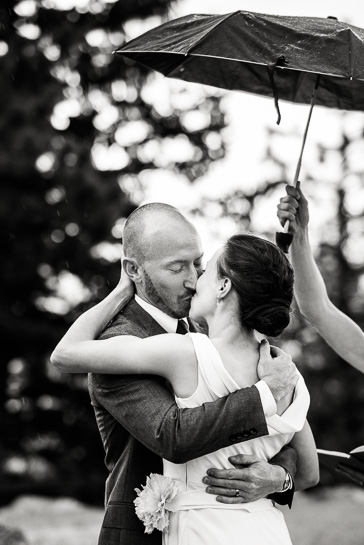 Denver wedding photojournalist captures Bride and groom share first kiss in the rain at Boulder, Colorado wedding.