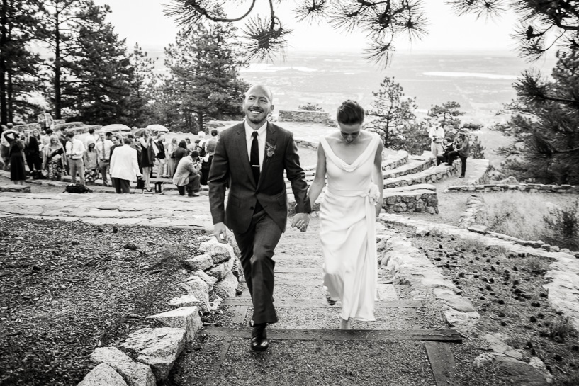 Bride and groom following ceremony at Sunrise Amphitheater, by Denver wedding photojournalist.
