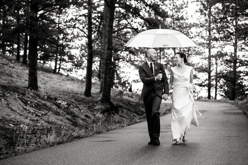Bride and groom walk under umbrella in the rain after Boulder, Colorado wedding.