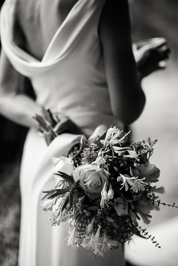 Black and white image of bride casually holding bouquet at Boulder wedding.