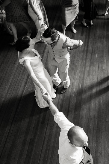 Bride does not let go of groom's hand during wedding reception.