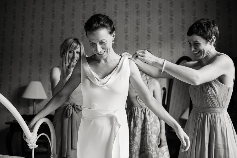 Bride putting on dress preparing for wedding at the Boulderado Hotel by Denver wedding photojournalist.