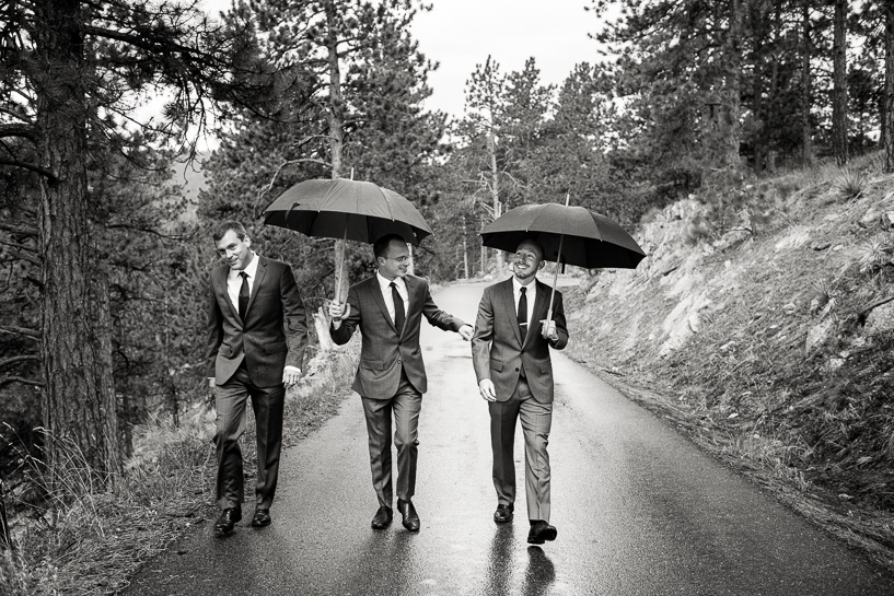 Groom and friends walk in the rain to Sunrise Amphitheater wedding in Boulder, Colorado.