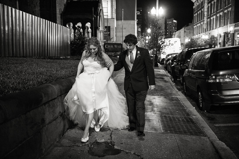 Denver documentary wedding photographer captures bride and groom side stepping puddles on a rainy night in New Orleans.
