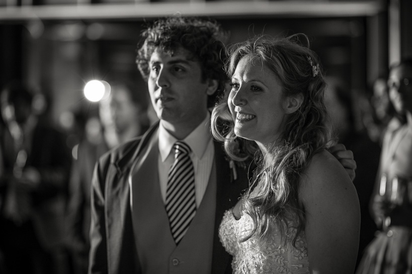 Natural black and white Denver wedding photography of bride and groom listening to toasts.