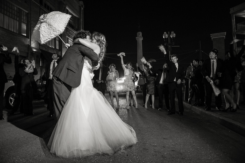 Embracing in the street after a New Orleans wedding by Denver black and white wedding photographer.