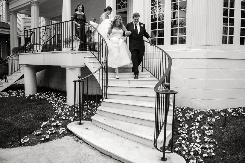 Bride and father descend steps by Denver black and white wedding photographer.
