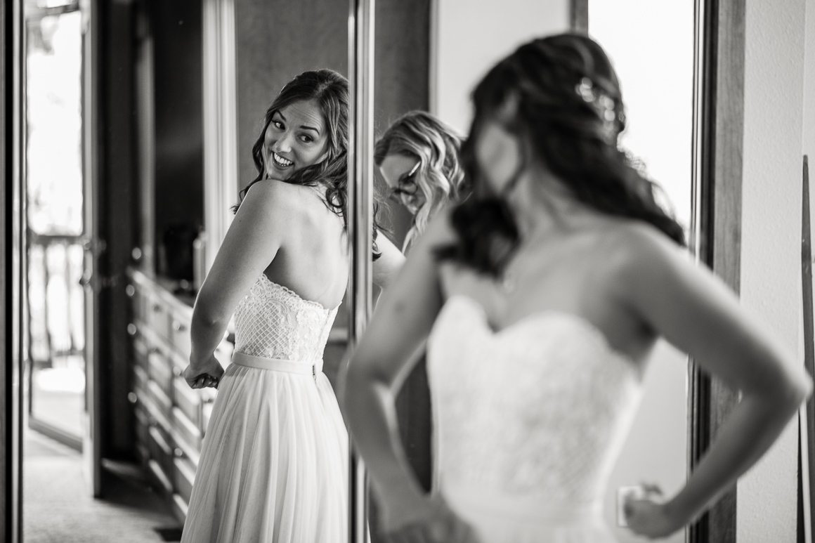 Colorado bride checks the back of her dress while preparing for a Longmont wedding ceremony.