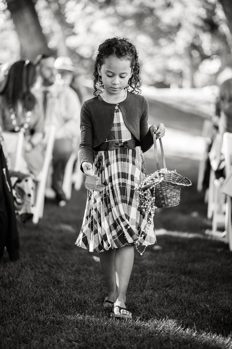 Flower girl drops pedals before a Colorado country wedding.