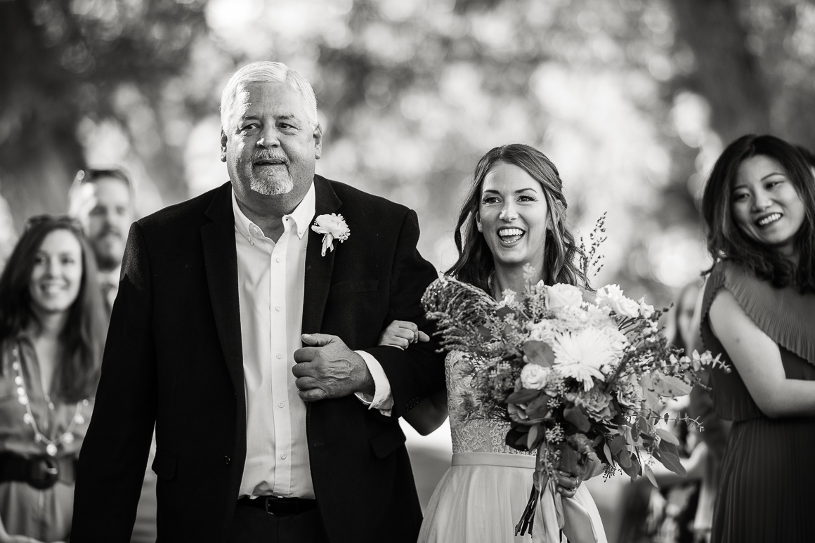 Colorado bride and her father walk down the aisle at their outdoor Longmont wedding.