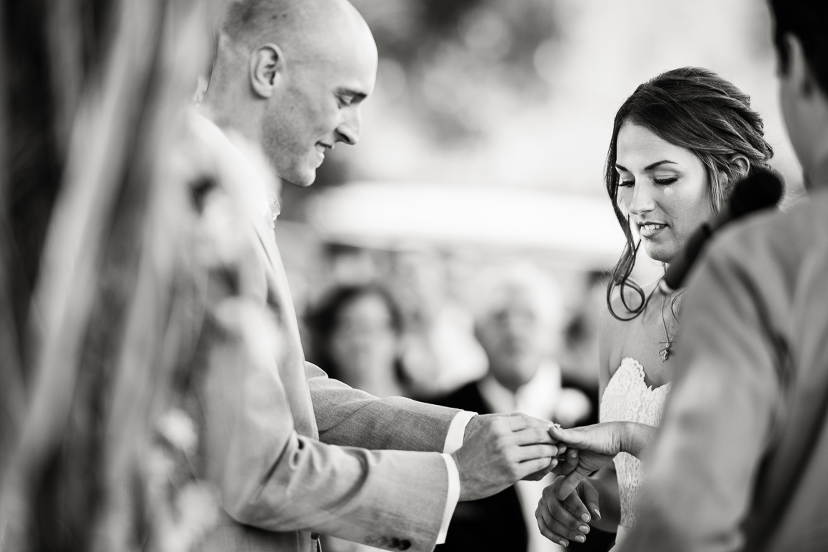 Groom slips on ring during a country wedding in Longmont Colorado.