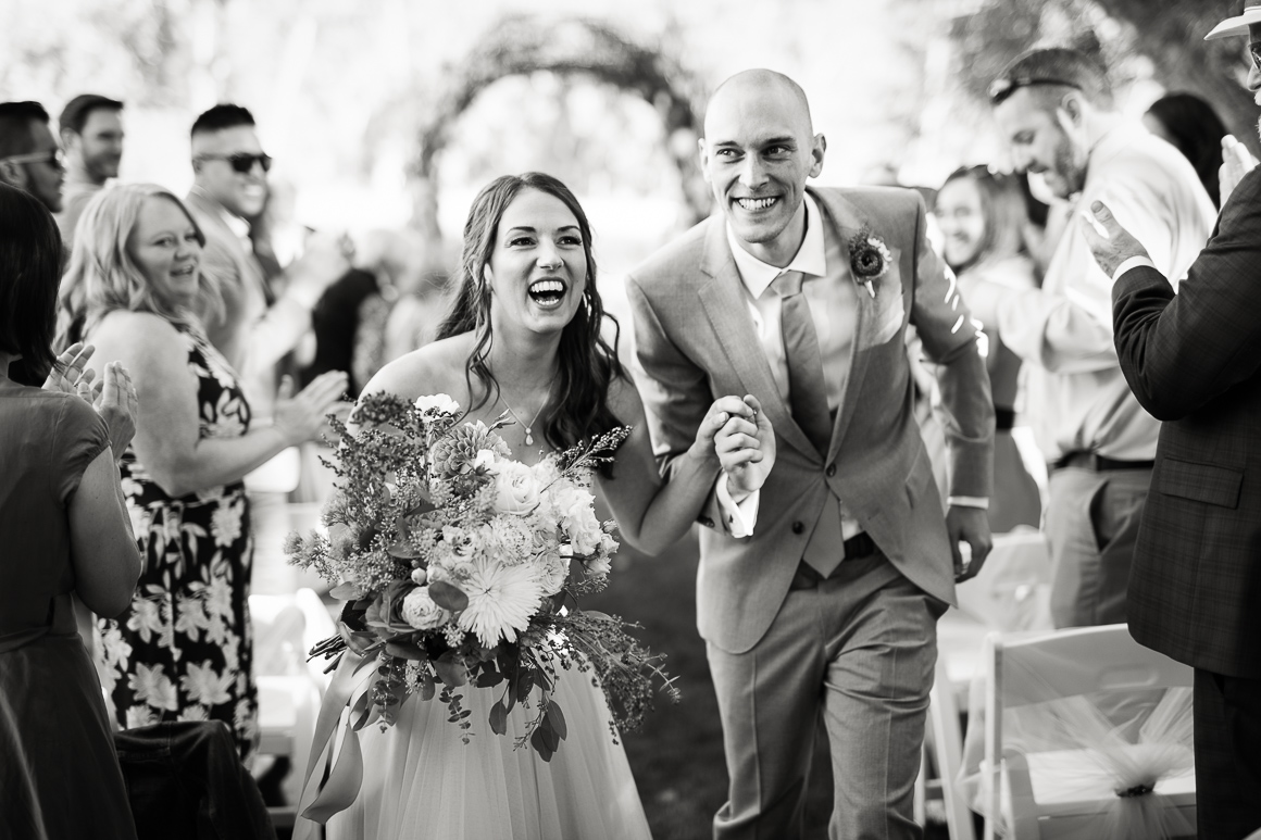 Colorado bride and groom run down the aisle after their Front Range wedding in Longmont.