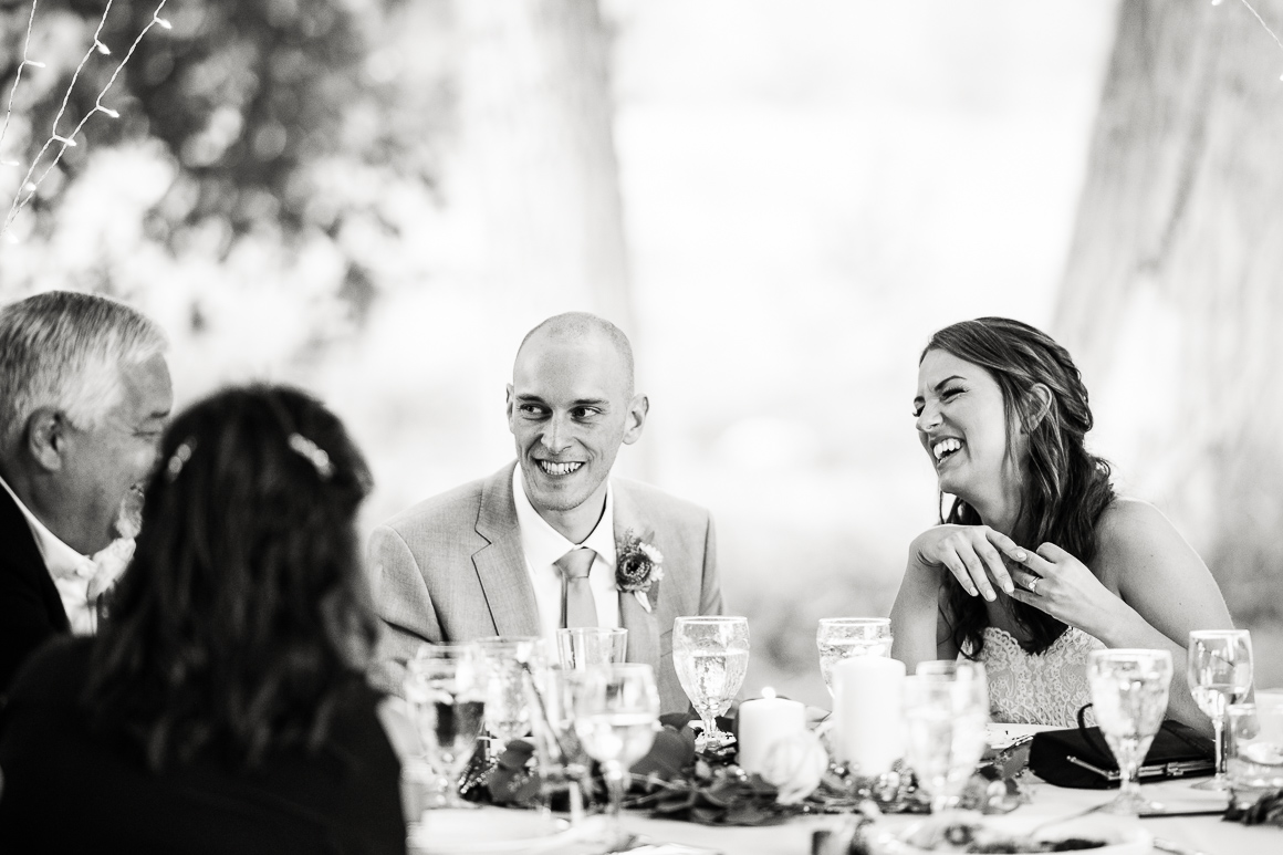 Denver bride and groom laugh with her father at a Longmont wedding reception.