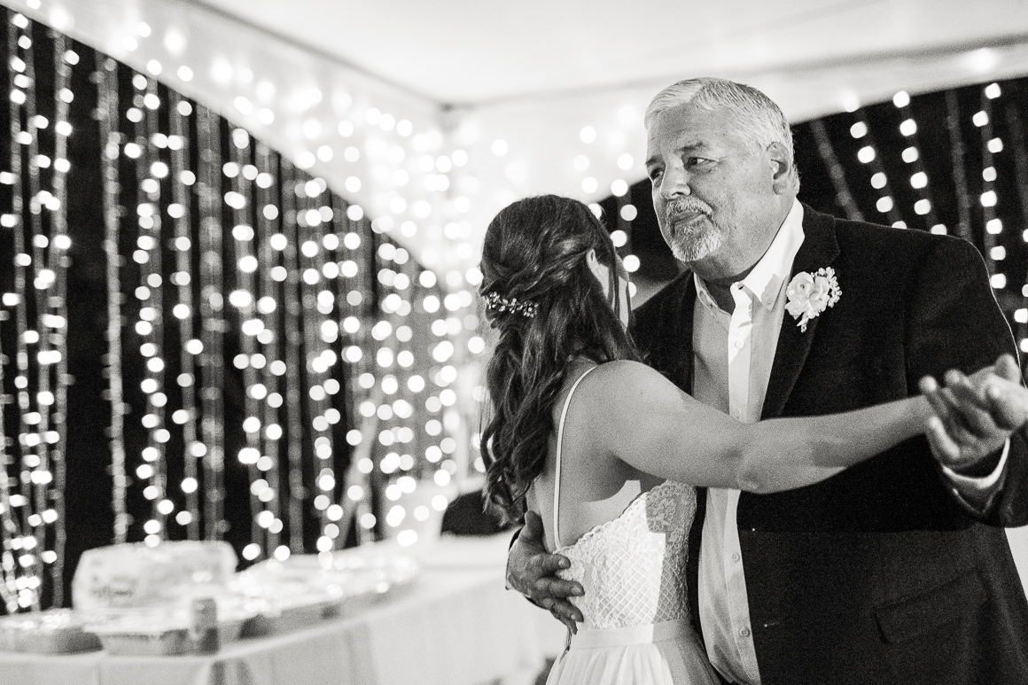 Bride and her father dance under a wedding tent with lights.