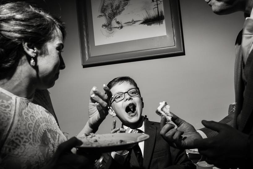 wedding couple feeds cake to young boy