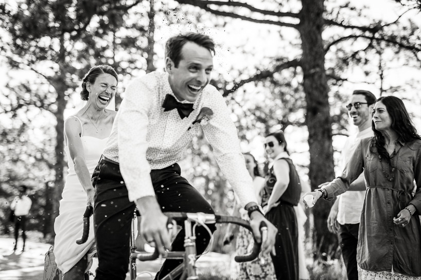 Denver wedding photojournalist captures bride and groom riding on tandem bike through birdseed