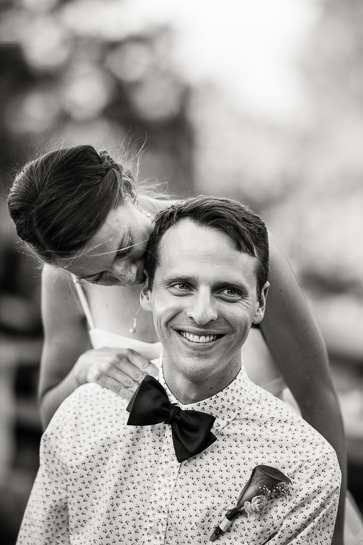 bride whispers to groom in bowtie