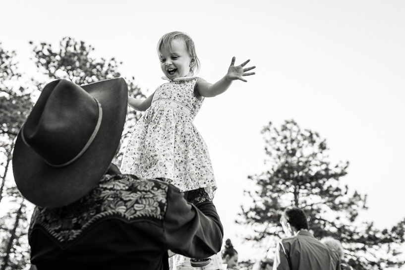 Father holds daughter aloft at Sunrise Amphitheater by Denver wedding photojournalist