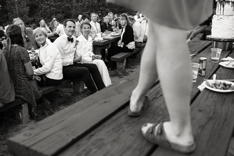 Maid of honor toasts bride while standing atop a picnic table.