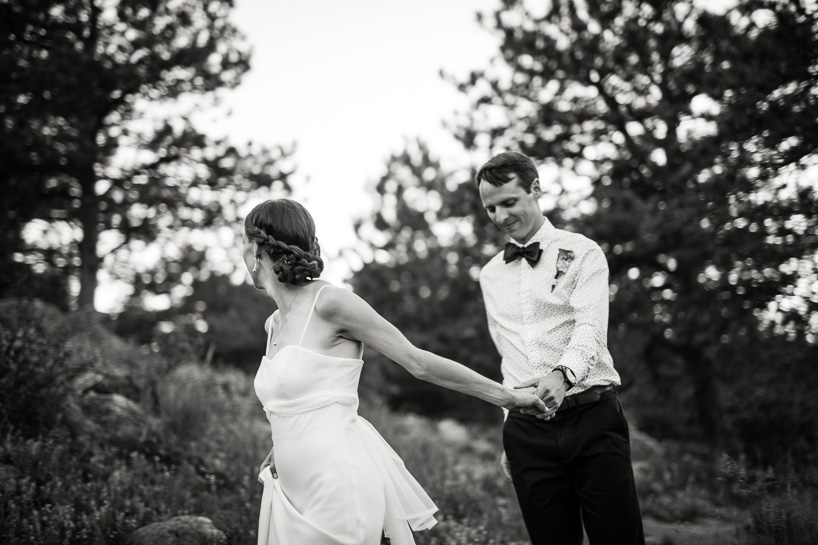 Bride and groom walk in the woods near Flagstaff Drive in Boulder