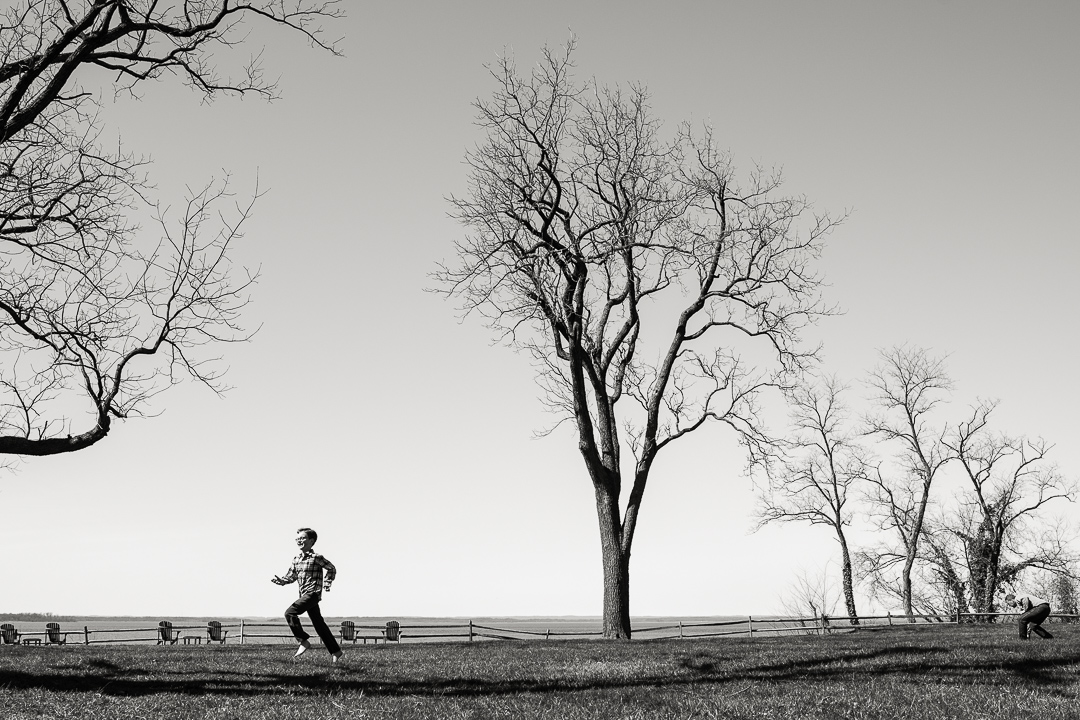 Boy runs through grass on the shore of the Chesapeake Bay.