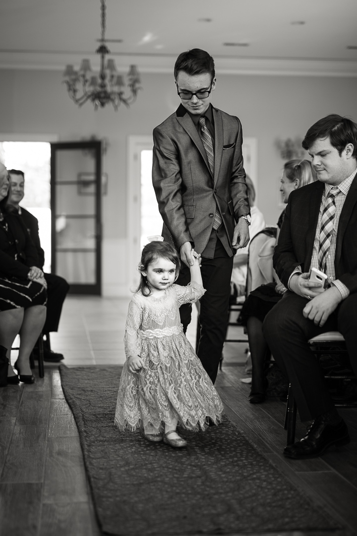 Very young flower girl walks down the aisle at wedding