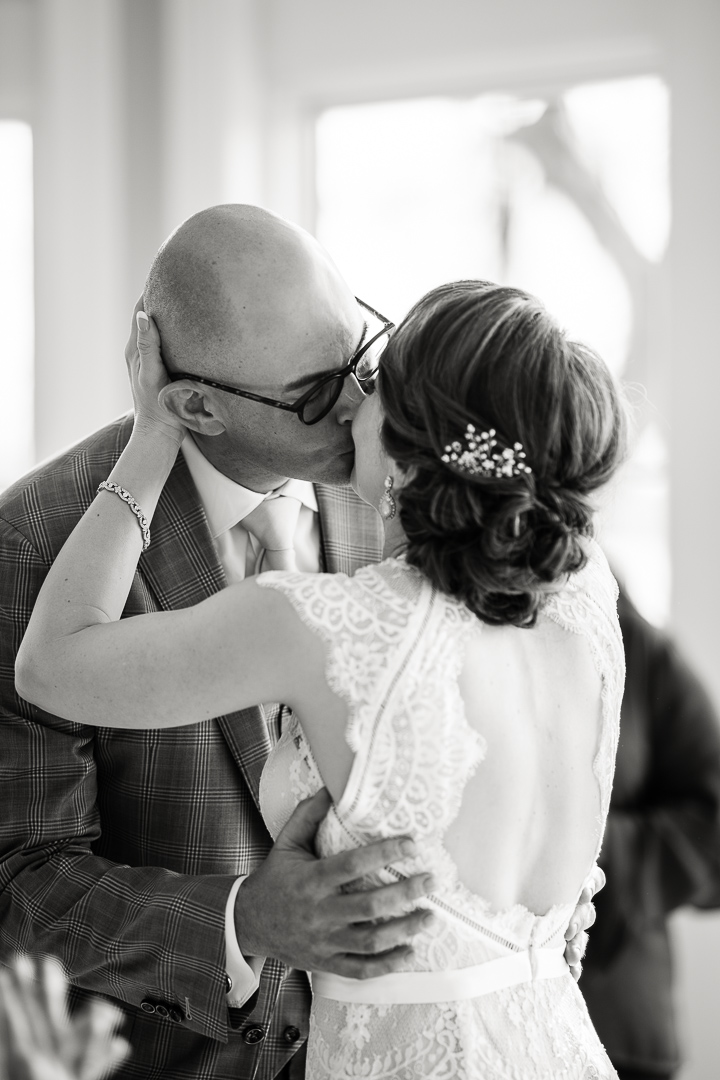 high key black and white image of wedding kiss