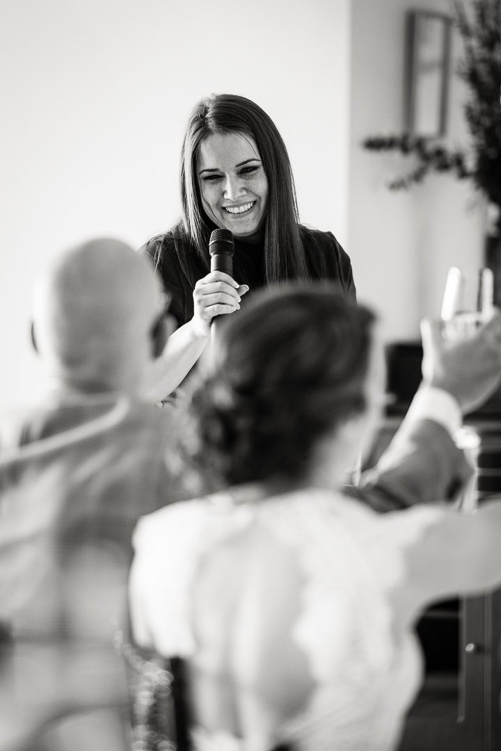 Bride's friend gives toast in black and white image by Colorado wedding photojournalist