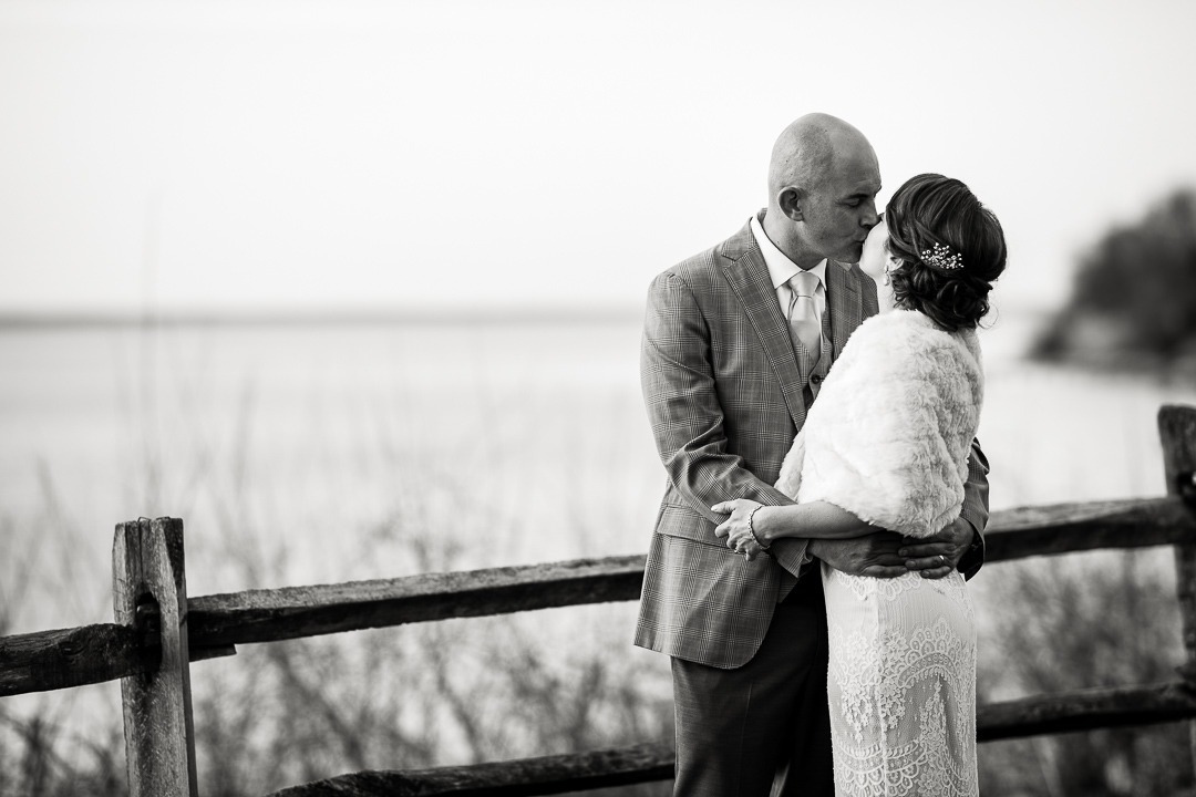 Wedding couple kiss near Chesapeake Bay at Great Oak Manor in Chestertown, Maryland.