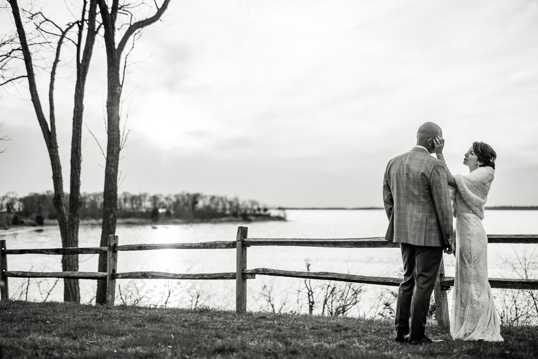 Candid image of wedding couple on the shore of Chesapeake Bay at Great Oak Manor in Chestertown, Maryland.