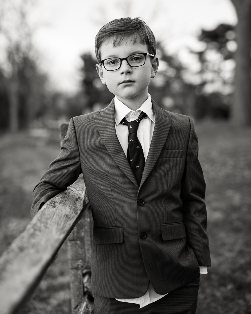 black and white image of boy wearing suit at wedding in early spring