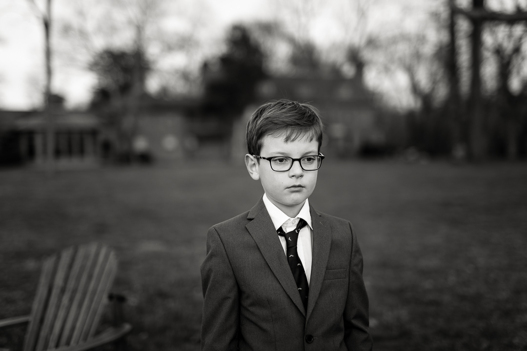 black and white image of boy in suit on lawn at dusk